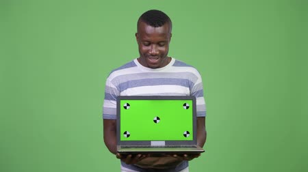 átnyújtás : Young happy African man looking while showing laptop
