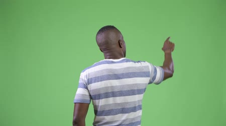 looking distance : Rear view of young African man directing and pointing finger