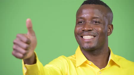 human like : Young happy African businessman thinking while giving thumbs up