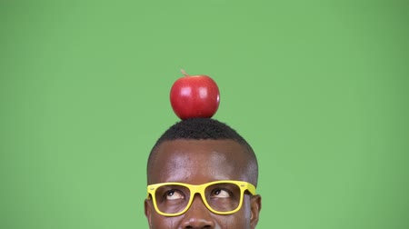мысли : Young African nerd businessman wearing eyeglasses with apple on top of head
