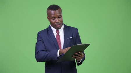 átnyújtás : Young happy African businessman explaining while holding clipboard