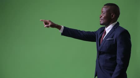 looking distance : Profile view of young African businessman pointing finger Stock Footage
