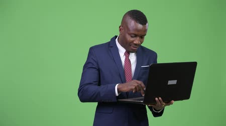 podnikatel : Young happy African businessman using laptop