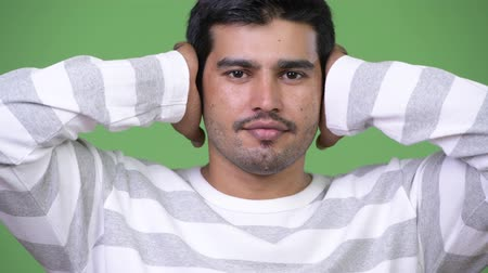 bilge : Young handsome Persian man covering ears as three wise monkeys concept