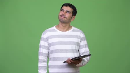 chroma key : Young handsome Persian man using digital tablet Stock Footage