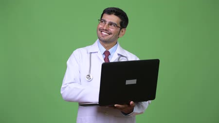 ближневосточный : Young handsome Persian man doctor using laptop