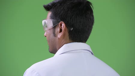 over the shoulder view : Profile view of young handsome Persian man doctor wearing protective glasses looking back Stock Footage