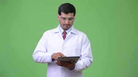 hand on chin : Young handsome Persian man doctor wearing protective glasses using digital tablet
