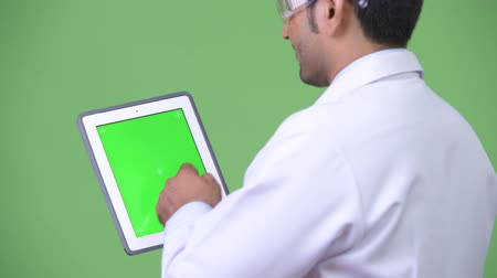 lado : Young handsome Persian man doctor wearing protective glasses showing digital tablet