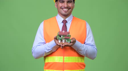figurka : Young handsome Persian man construction worker holding house figurine Dostupné videozáznamy
