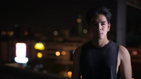 kolsuz : Portrait of young handsome Asian man thinking outdoors at night