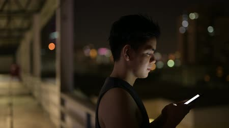 biceps : Young happy Asian man using phone against view of the city at night