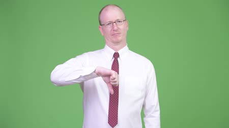 disappointment : Angry mature bald businessman giving thumbs down