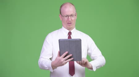 связать : Happy mature bald businessman using digital tablet