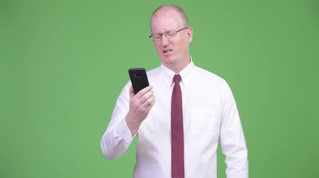 white shirt : Stressed mature bald businessman using phone and getting bad news