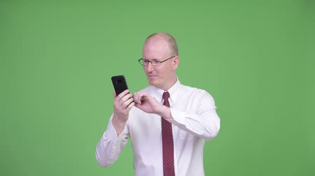 adam : Happy mature bald businessman using phone and looking shocked