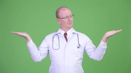 comparar : Mature bald man doctor comparing something Stock Footage