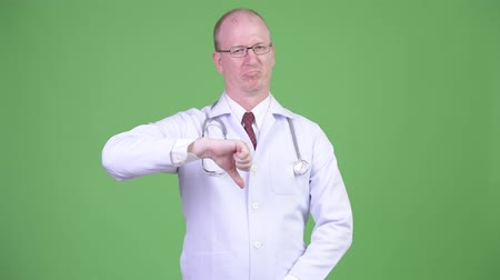 disapprove : Sad mature bald man doctor giving thumbs down