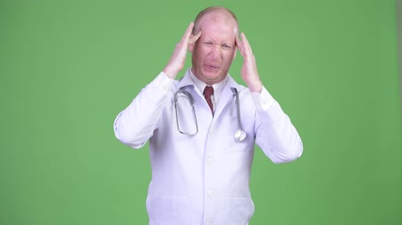 dor de cabeça : Stressed mature bald man doctor having headache Stock Footage