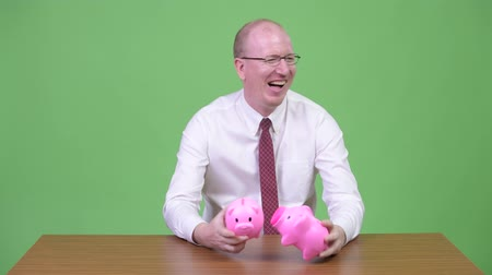 culpa : Mature bald businessman playing with two piggy banks and looking guilty against wooden table