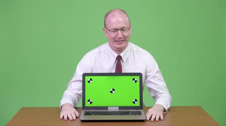 errado : Mature bald businessman showing laptop and looking guilty against wooden table Stock Footage
