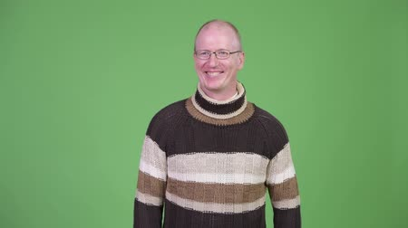 do widzenia : Happy mature bald man waving hand and wearing turtleneck sweater