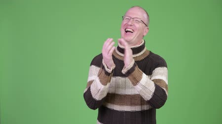 ovation : Happy mature bald man with turtleneck sweater clapping hands while thinking Stock Footage