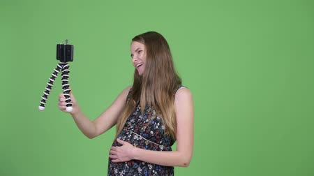 tripod shot : Young happy pregnant woman vlogging with phone Stock Footage