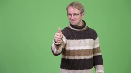 middle : Studio shot of happy handsome man giving thumbs up Stock Footage