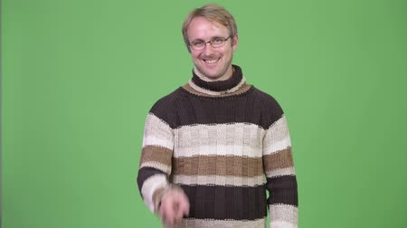 на камеру : Studio shot of happy handsome man pointing to camera Стоковые видеозаписи