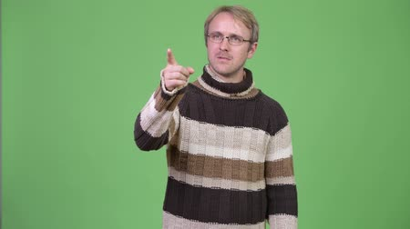 copyspace : Studio shot of blonde handsome man thinking while pointing finger
