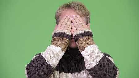 chroma key : Studio shot of blonde handsome man covering eyes as three wise monkeys concept