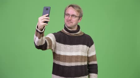 середине взрослых : Studio shot of happy handsome man taking selfie Стоковые видеозаписи