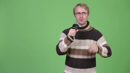 culpa : Studio shot of blonde handsome man using microphone and looking guilty