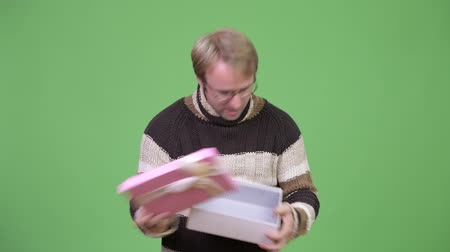 refusing : Studio shot of stressed man opening empty gift box and looking disappointed