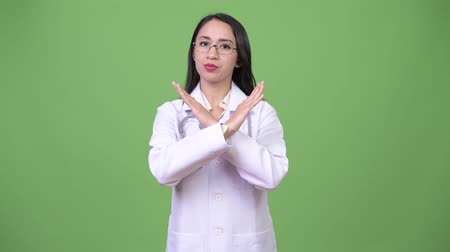 brasão : Young beautiful Asian woman doctor with stop gesture Stock Footage