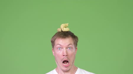 poo : Young handsome man with poo on head Stock Footage