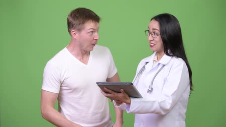 フィンランド語 : Young Asian woman doctor giving consultation to young man patient