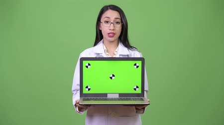 átnyújtás : Young beautiful Asian woman doctor showing laptop Stock mozgókép