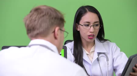 フィンランド語 : Young Asian woman doctor having meeting with young man doctor