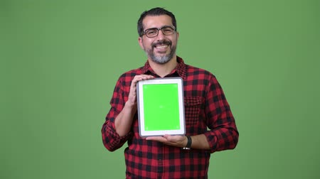 middle : Handsome Persian bearded man showing digital tablet