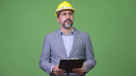 hardhat : Handsome Persian bearded businessman as engineer thinking with clipboard