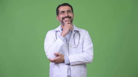 hand on chin : Handsome happy Persian bearded man doctor smiling while thinking