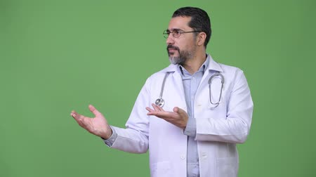 stethoscoop : Handsome Persian bearded man doctor showing something Stockvideo