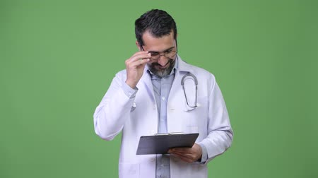 panoya : Handsome happy Persian bearded man doctor reading clipboard Stok Video