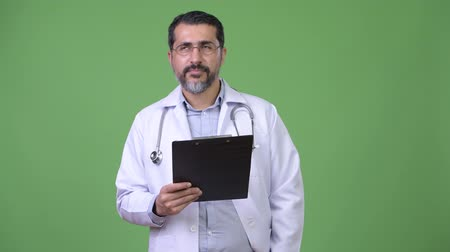 середине взрослых : Handsome Persian bearded man doctor thinking while holding clipboard Стоковые видеозаписи