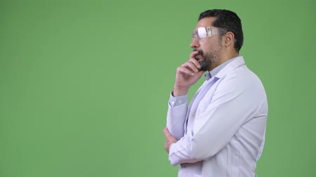 hand on chin : Profile view of handsome Persian bearded man doctor wearing protective glasses and thinking
