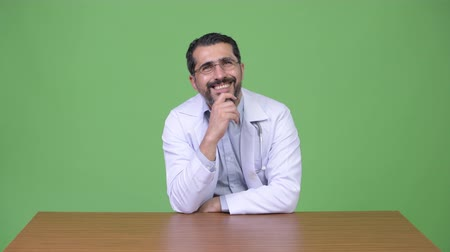 hand on chin : Handsome Persian bearded man doctor smiling while thinking