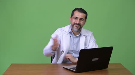 apresentador : Handsome Persian bearded man doctor working with laptop and greeting Vídeos