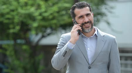 ближневосточный : Handsome Persian bearded businessman talking on phone in the streets outdoors Стоковые видеозаписи